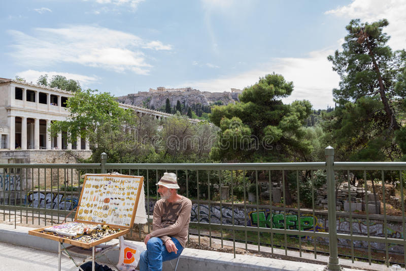 Street vendor selling jewellery near Stoa of Attalos of the Ancient Agora of Athens with the Acropolis in the background stock photos