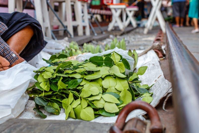 Street vendor selling Kaffir lime leaves for cooking at famous Maeklong railway market. Samut Songkhram province, Thailand royalty free stock photo
