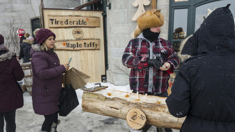 Street vendor selling maple toffee made of hot maple syrup in Quebec, Canada. stock photos