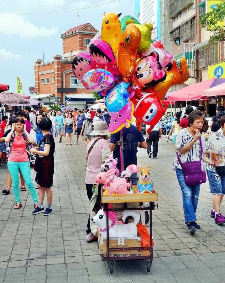 Street Vendor Sells Balloons. KAOHSIUNG, TAIWAN -- JUNE 27, 2019: A street vendor sells balloons on the main tourist street on Chijin Island stock photo