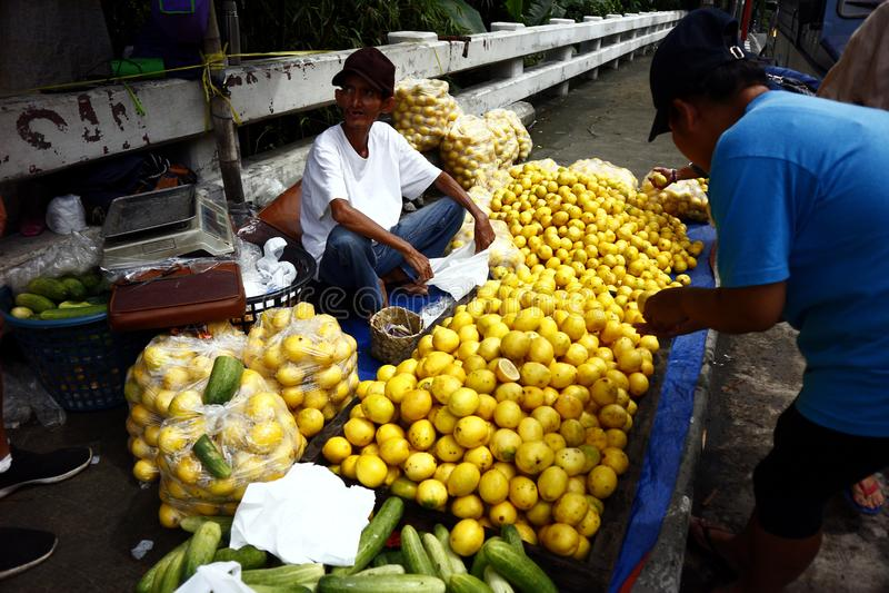 A street vendor sells fresh and ripe lemon at a sidewalk along a highway. ANTIPOLO CITY, PHILIPPINES – JULY 17, 2019: A street vendor sells fresh and ripe stock image