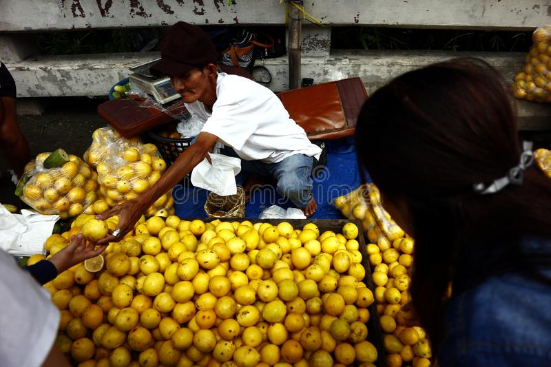 A street vendor sells fresh and ripe lemon at a sidewalk along a highway. ANTIPOLO CITY, PHILIPPINES – JULY 17, 2019: A street vendor sells fresh and ripe royalty free stock photography