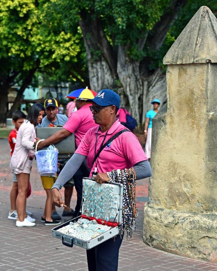 Street vendor sells rosaries and Larimar gem stones in Santo Domingo. Santo Domingo, Dominican Republic - February 7, 2019: Street vendor peddles Catholic stock images