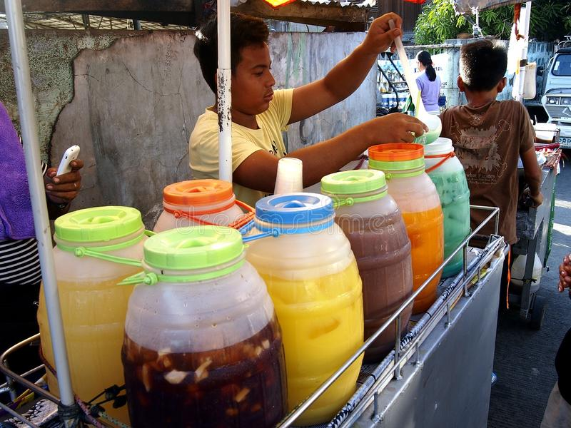 A street vendor sells a variety of fruit juice and other refreshments on his beverage cart at a street in Antipolo City. ANTIPOLO CITY, PHILIPPINES - APRIL 24 royalty free stock photos