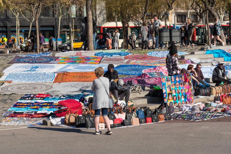 Street vendors in Barcelona, Spain. BARCELONA, SPAIN, March 2018: street vendors along the promenade of Barcelona trying to sell their patterned shawls, fake stock photography