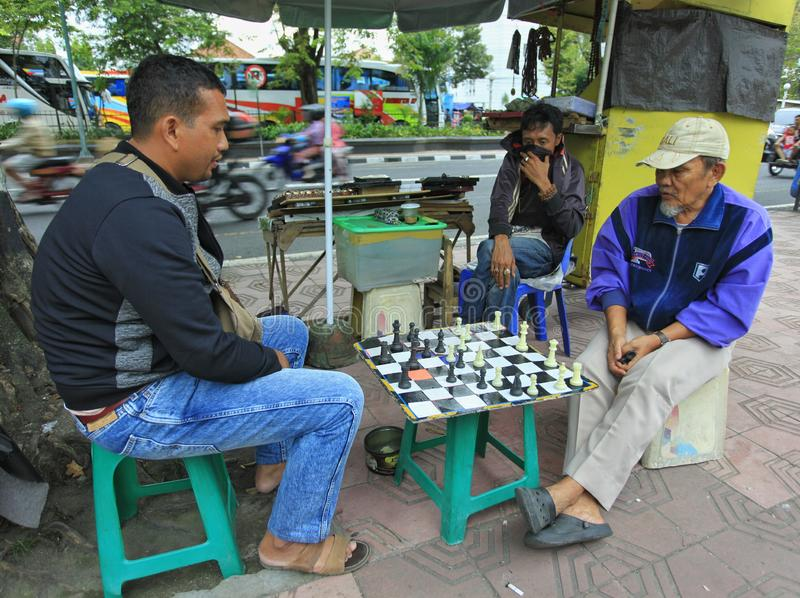 Street vendors fill their free time when selling by playing chess stock images