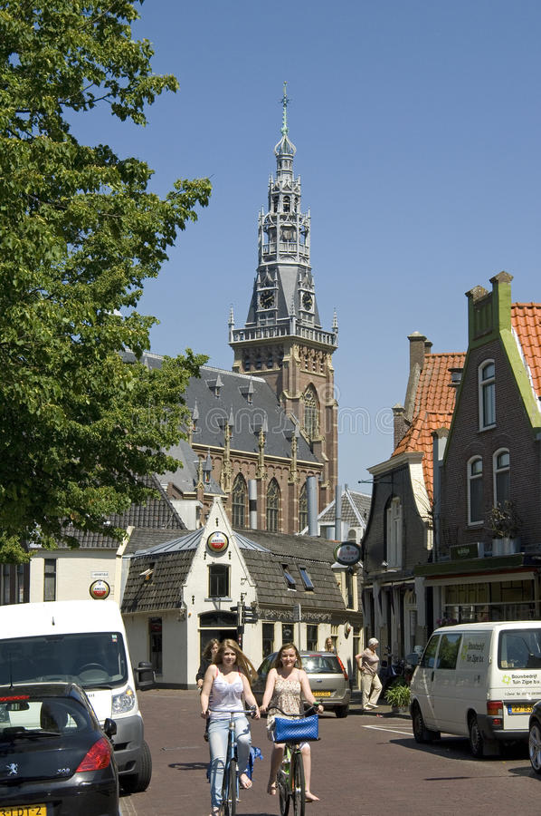 Street view, biking teens, church tower, Schagen. Netherlands, North-Holland, West Friesland region, city, small town Schagen: Street scene in the historic stock photography