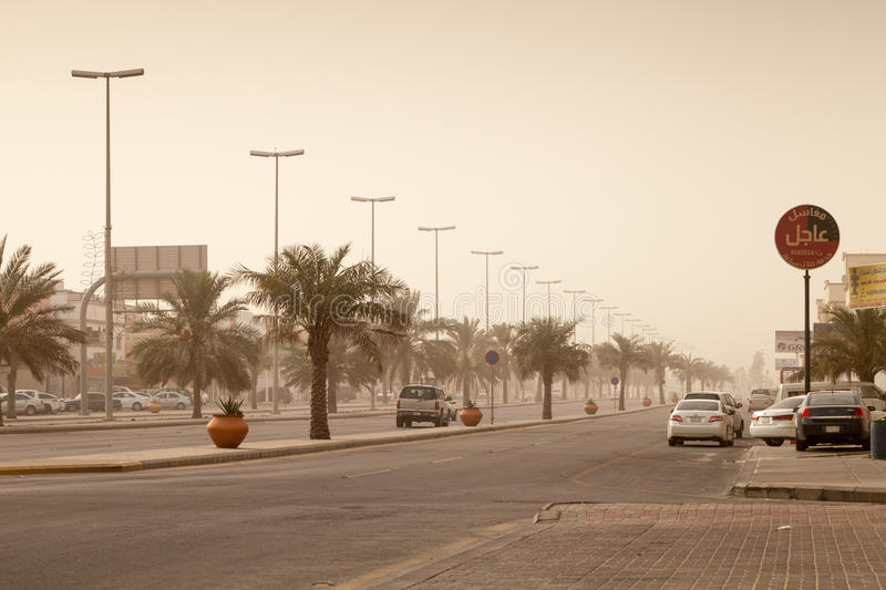 Street view with cars and palms, dust storm in Saudi Arabia stock image