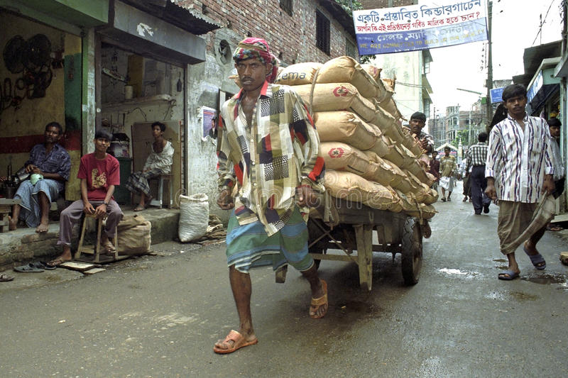 Street view of Dhaka with porter lugging cement royalty free stock photography