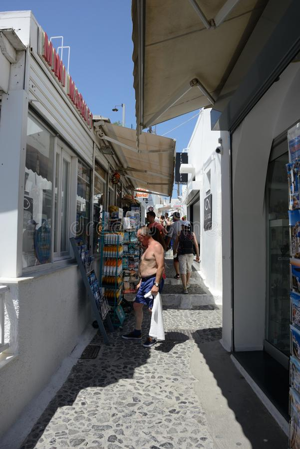 Street view of Fira with people walking and man without shirt looking the souvenir stock photography