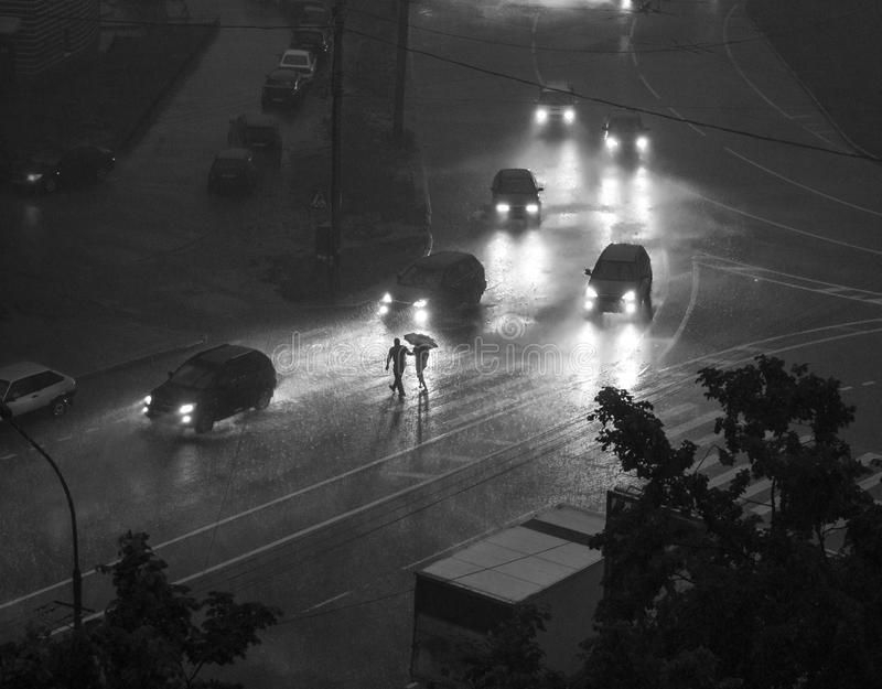 Street view, late evening, heavy rain, umbrella (BW) royalty free stock photography