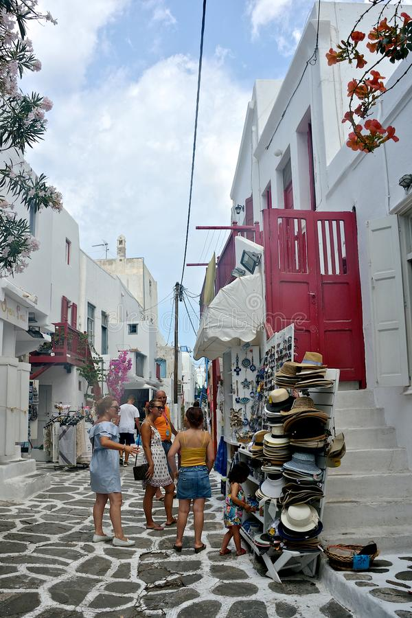 Street view of Mykonos with people walking and tourist shops with clothes and hat stock photography