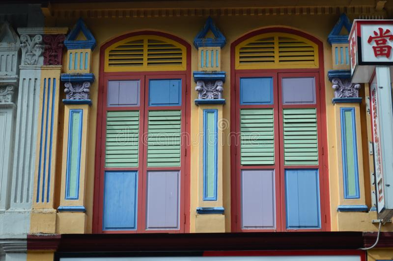 Detailed view of pastel and pale colored colonial windows and shutters on buffalo road Little India , Singapore royalty free stock images