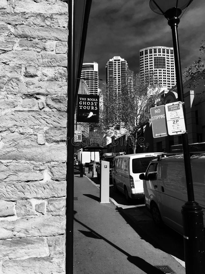 Street view, The Rocks. Street buildings colonial Sydney bricks skyscrapers highrise black and white parked cars stock photo