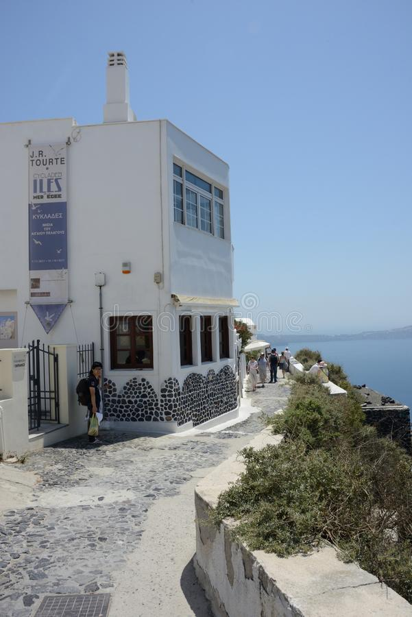 street view of Santorini with one white building sea front and some tourists walking royalty free stock images