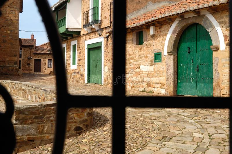 Street of the Village of Castrillo de los Polvazares seen from a window with iron bars, Leon province, Spain stock photo