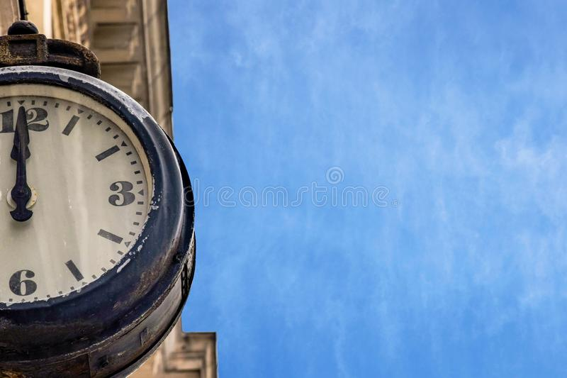 Street vintage clock on an old building against a blue sky with aerial clouds royalty free stock photo