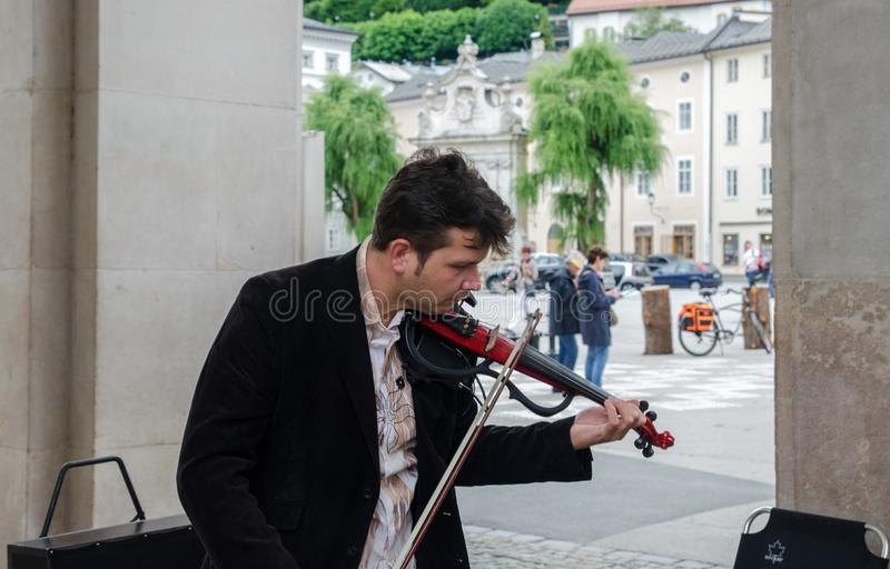 Violin player play classical music on city street. Salzburg. royalty free stock photography