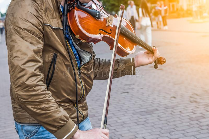 Street violinist plays the violin at noon. Autumn day stock photography