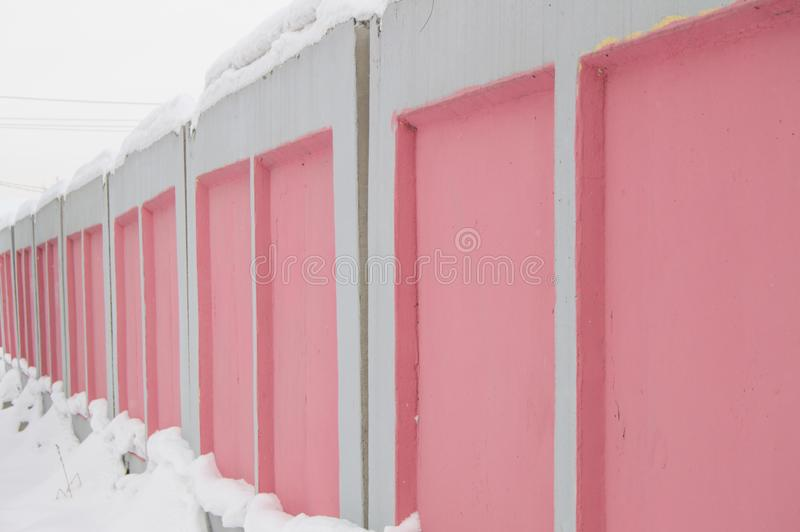 Street wall, fence of concrete slabs pink and white, fence construction in the city, winter, side view royalty free stock photo