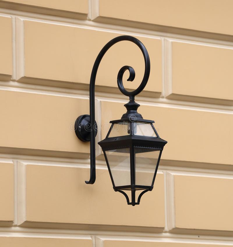 Street wall-mounted electric lantern antique. The street wall-mounted electric lantern antique royalty free stock photography