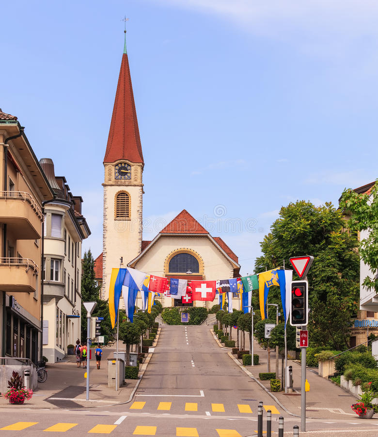 Street in Wallisellen decorated with flags for the Swiss National Day. Wallisellen, Switzerland - 30 July, 2017: Kirchstrasse street decorated with flags for the stock photography