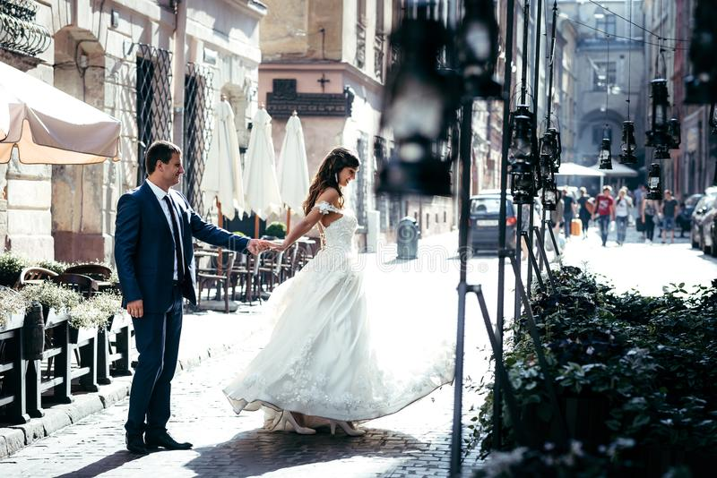 Street and wedding concept. Adorable smiling just married are dancing in the sun. Street and wedding concept. Adorable smiling just married are dancing in the royalty free stock images