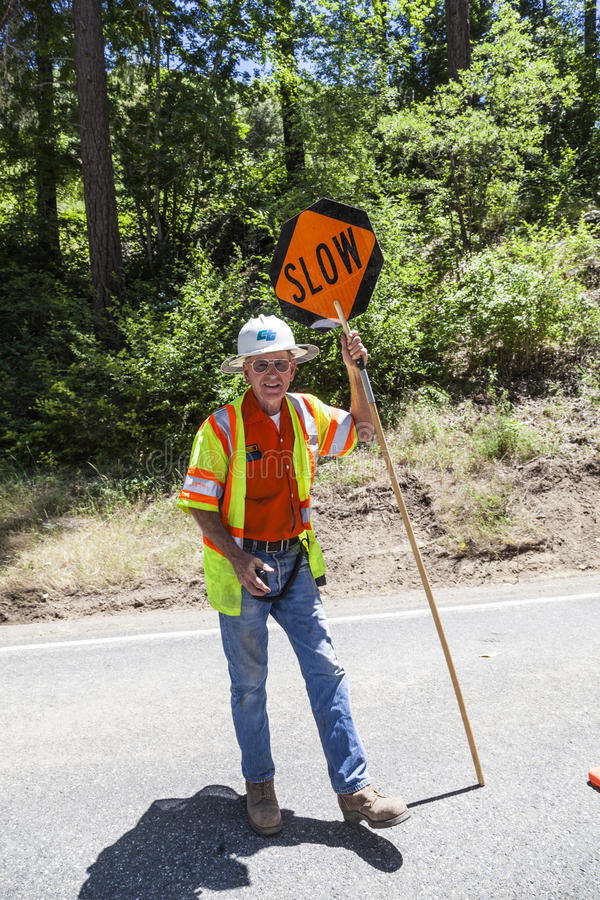 Street worker shows slow sign to reduce speed stock image