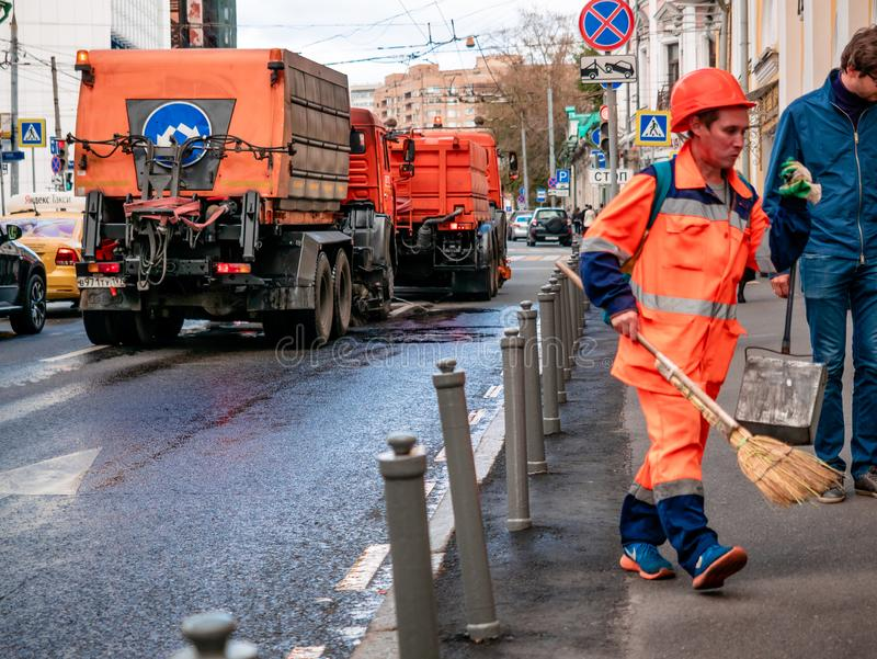 Street worker sweeping the sidewalk in an orange uniform. In the background, special watering machines are visible for cleaning s royalty free stock images