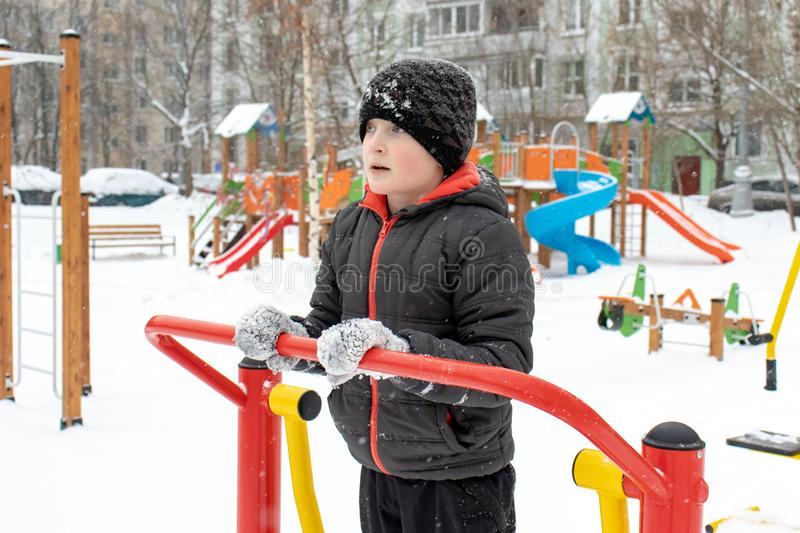 Street workout equipment in winter, outdoor sport fitness and bodybuilding. Boy in a sport playground doing workout exercises. Outdoor in winter royalty free stock photography