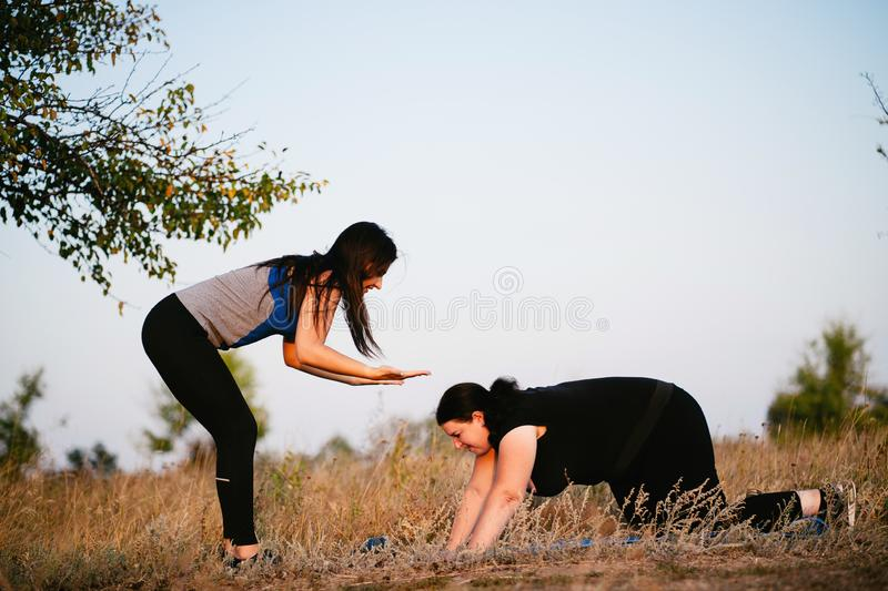 Overweight woman training with trainer support. Street workout, motivation, sport, outdoor activity, healthy lifestyle concept. Personal trainer giving royalty free stock image