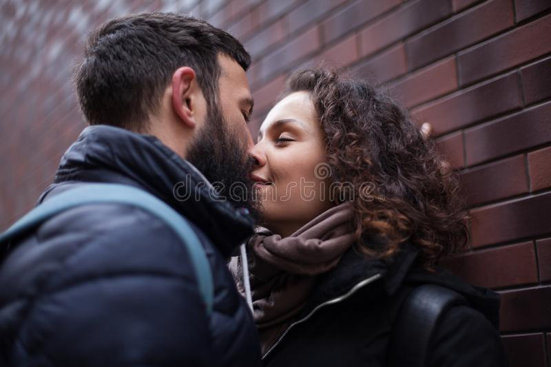Street, young couple deeply in love, sharing a romantic kiss, close-up royalty free stock image