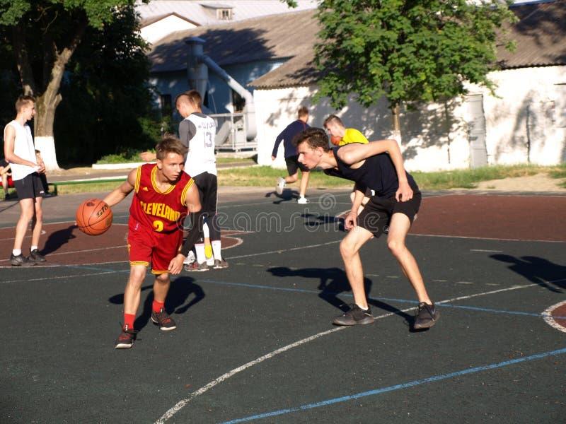 Streetball basketmatch med tv? spelare, ton?ringar flicka och pojke med bollen, utomhus- stadsbasketdomstol arkivfoto
