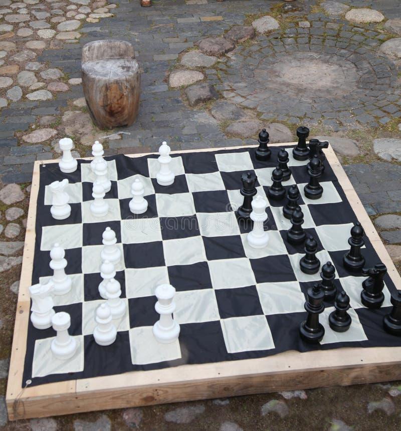 Streetchess-Stücke an einem Quadrat Brett eines Schachspiels Eine ruhige Szene eines Schachmatches im Freien in einem Park stockfotografie