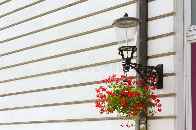 Streetlamp on a Historic Buildings Facade. Classic streetlamp on a historic buildings facade with a flowerpot hanging from its support royalty free stock photos