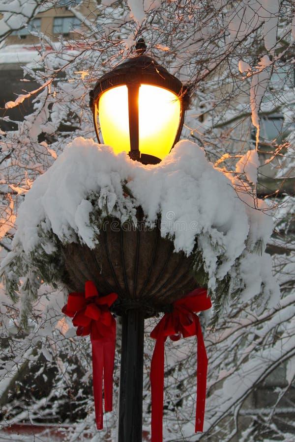Streetlamp som dekoreras för jul som täckas i Ny-stupad snö arkivfoton