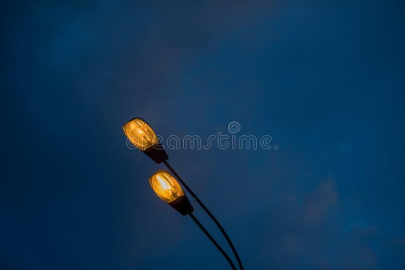 Streetlight mot bakgrunden av aftonhimlen Gul elljus mot bakgrunden av åskmoln arkivbild
