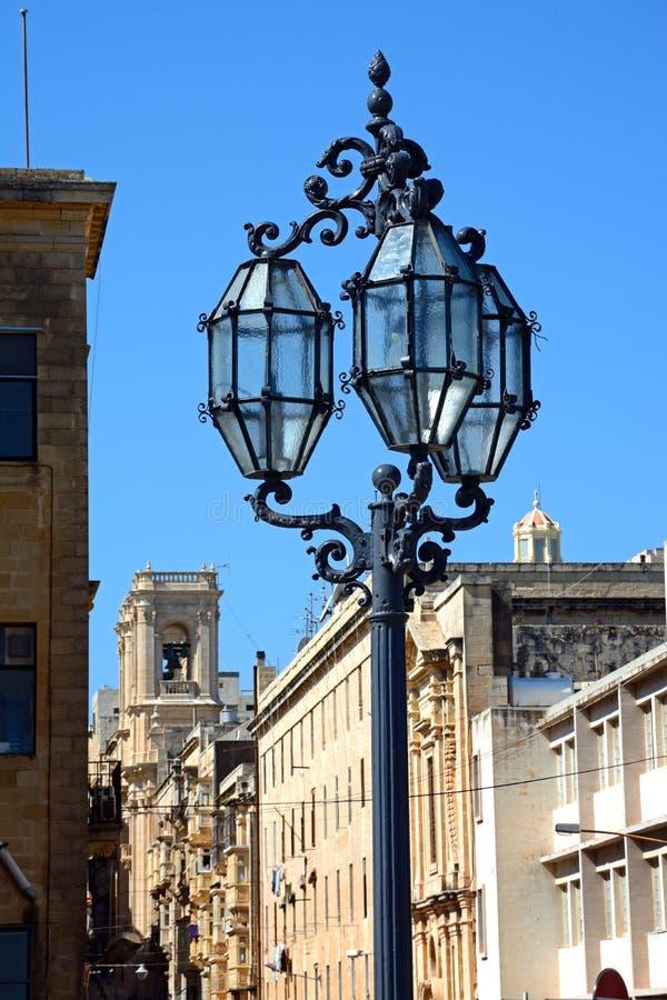 Streetlight and Public Registry, Valletta. Traditional wrought iron streetlight by Public Registry, Valletta, Malta, Europe royalty free stock photo