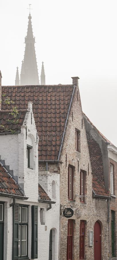 Streets of Bruges, Belgium - red tile roofs. This image shows a view of a street in Bruges, Belgium, Europe. We can see red tile roofs and a church tower in the royalty free stock photos