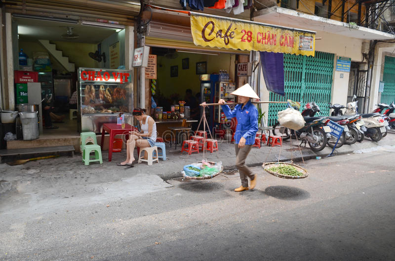 Streets of Hanoi. Fruit vendor walking by the streets of Hanoi,Vietnam royalty free stock images