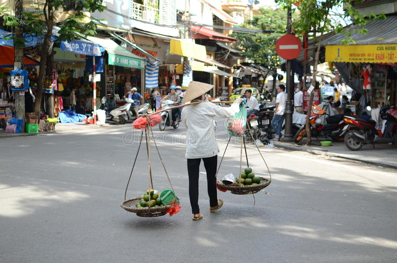 Streets of Hanoi. Fruit vendor walking by the streets of Hanoi,Vietnam stock photo