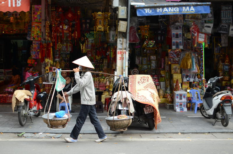 Streets of Hanoi. Fruit vendor walking by the streets of Hanoi,Vietnam stock photo