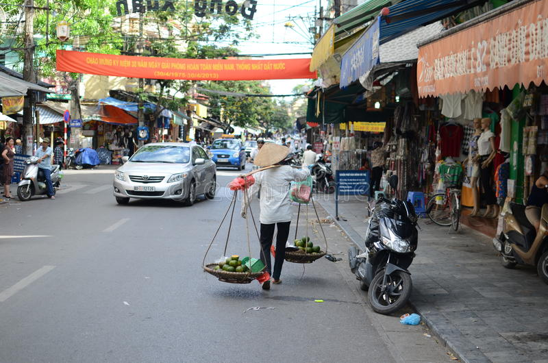 Streets of Hanoi. Fruit vendor walking by the streets of Hanoi,Vietnam royalty free stock photos