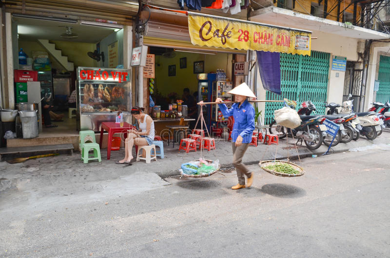Streets of Hanoi. Fruit vendor walking by the streets of Hanoi,Vietnam royalty free stock photo