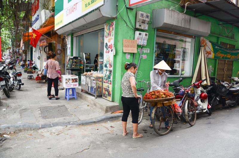 Streets of Hanoi. Fruit vendor walking by the streets of Hanoi,Vietnam stock images