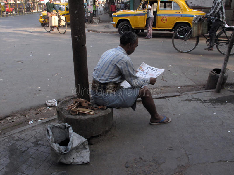 Streets of Kolkata, man reading the newspaper while ignoring everything around him stock images