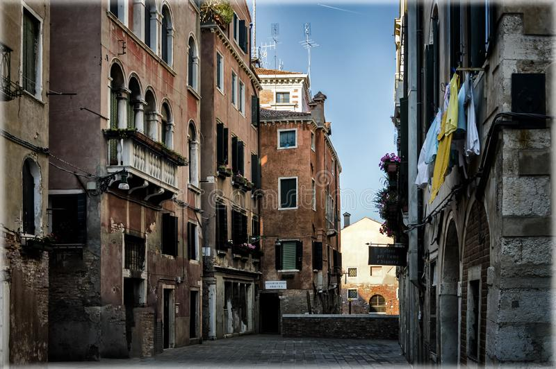 The streets of Venice, Italy. Ancient buildings with beautiful balconies and the church at the end of the street. stock photography
