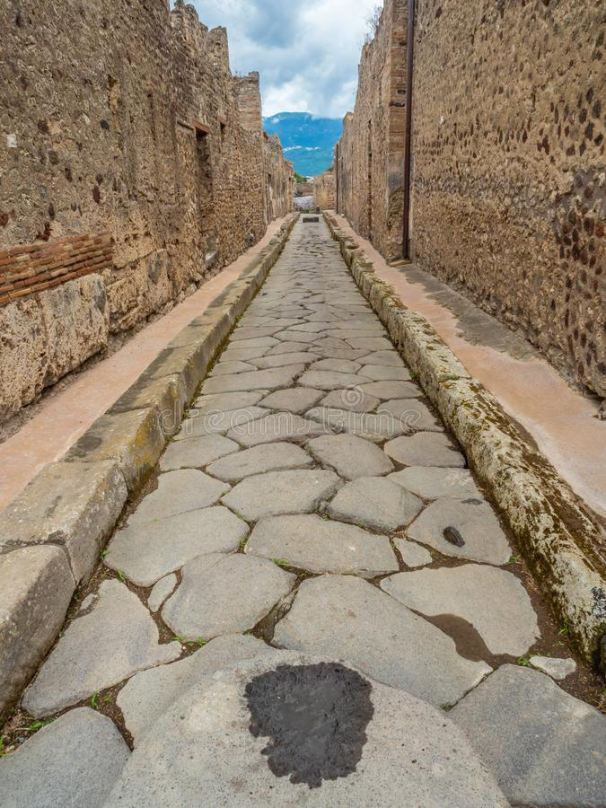 Streets and villas of Pompeii, Italy. World Heritage List. Cobbled street lined with ruined shops and villas in the ancient Roman city of Pompeii, near modern royalty free stock image