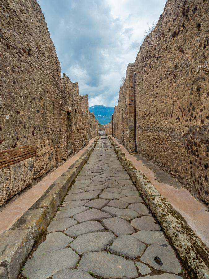 Streets and villas of Pompeii, Italy. World Heritage List. Cobbled street lined with ruined shops and villas in the ancient Roman city of Pompeii, near modern royalty free stock photo