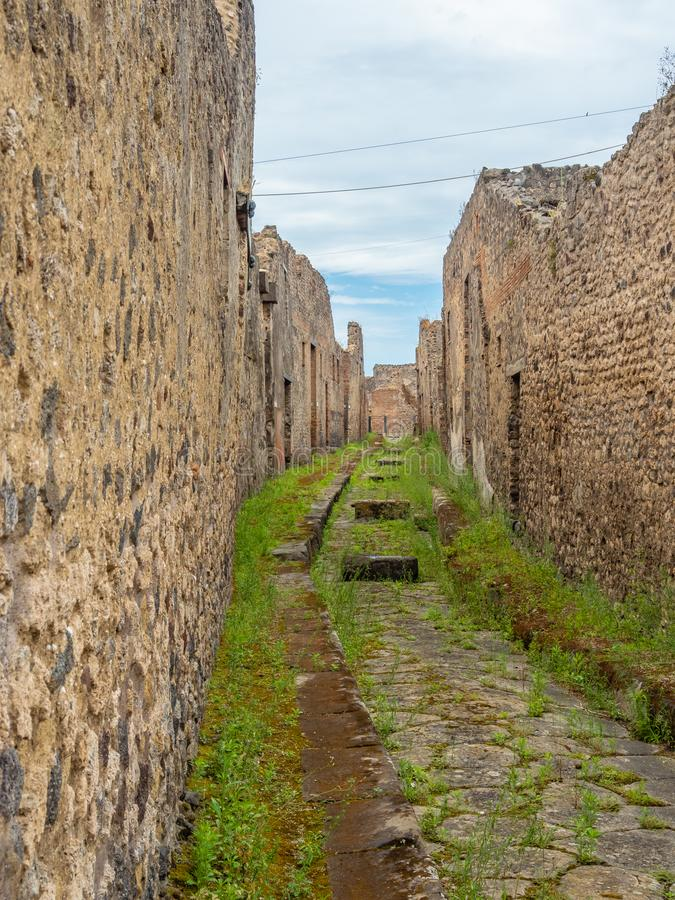 Streets and villas of Pompeii, Italy. World Heritage List. Cobbled street lined with ruined shops and villas in the ancient Roman city of Pompeii, near modern royalty free stock photos